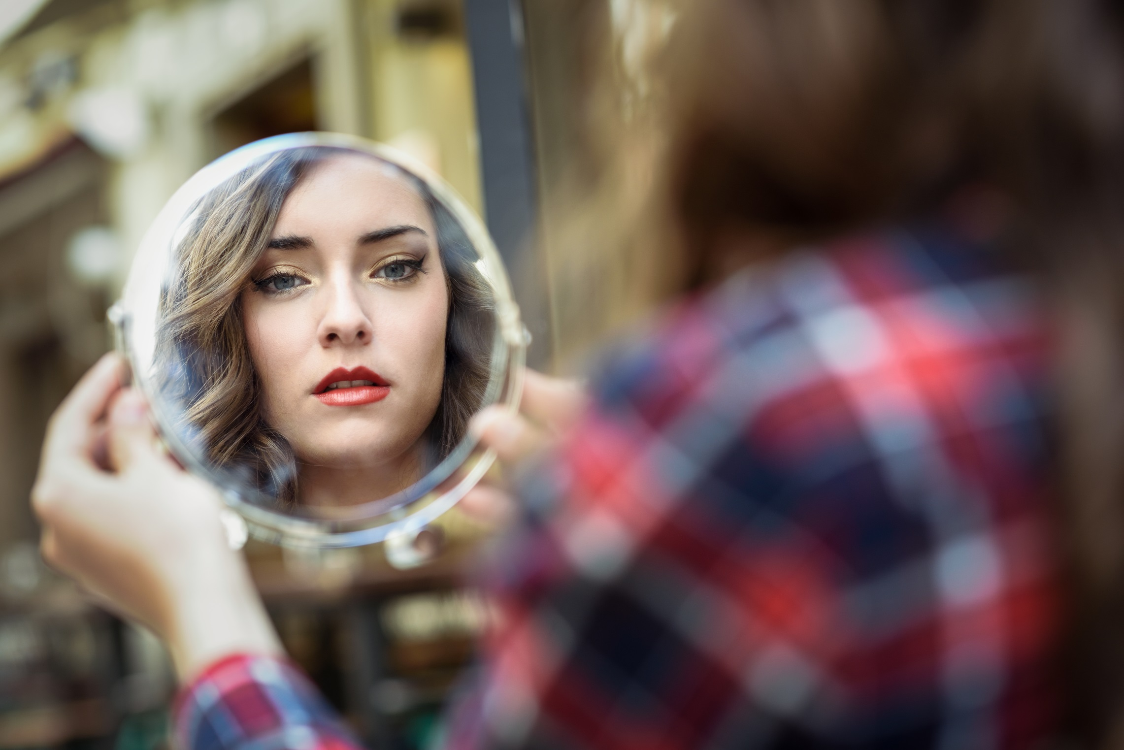 Portrait of young woman looking at herself in a little mirror in urban background.